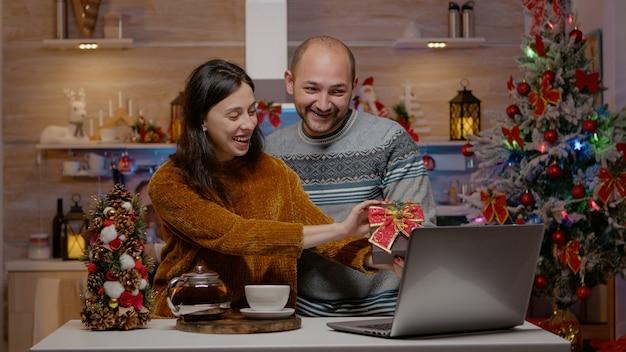 Świąteczna para dająca prezenty na wideokonferencji