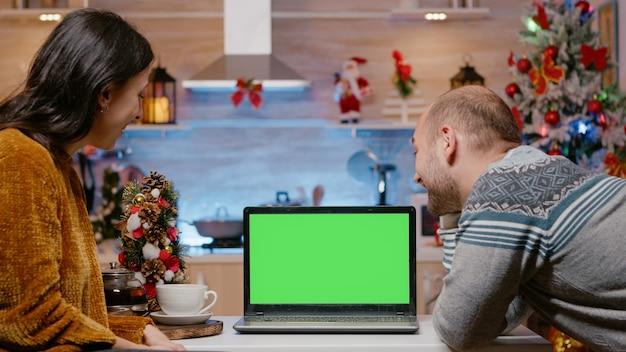 Świąteczna para patrząca na poziomy zielony ekran na laptopie