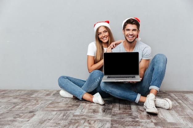 Świąteczna para pokazująca laptopa