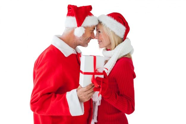 Świąteczna para uśmiecha się prezent i trzyma