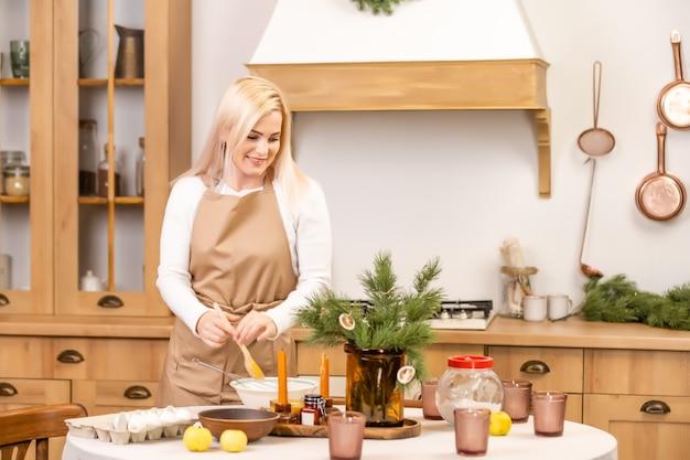 Świąteczna piekarnia. kobieta gotuje przed świętami bożego narodzenia. świąteczne jedzenie, proces gotowania, rodzinna koncepcja tradycji kulinarnych, świątecznych i noworocznych
