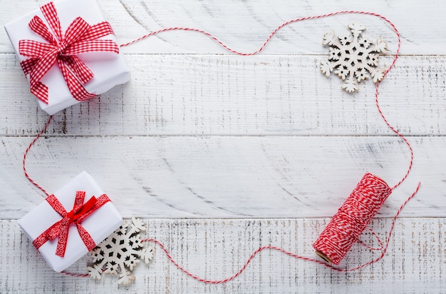 Świąteczna powierzchnia z czerwoną wstążką, zabawkami, pudełkami na prezenty i szyszkami na białym drewnianym starym stole powierzchniowym. selektywna ostrość.