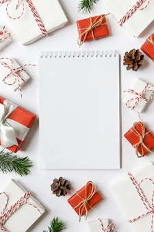 Świąteczna powierzchnia z pustym notatnikiem, czerwono-białe pudełka na prezenty ze wstążką, gałęzie jodły, szyszki na białej powierzchni. leżał na płasko. miejsce na tekst.