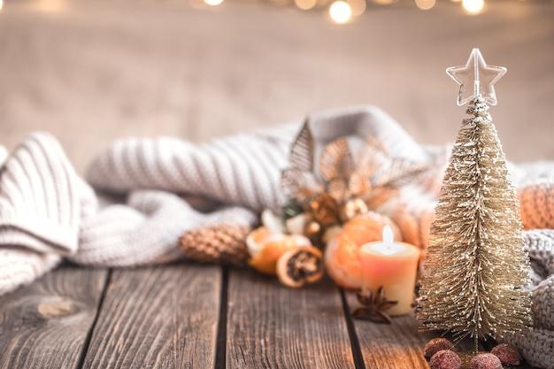 Świąteczna przytulna atmosfera bożego narodzenia z wystrojem domu i mandarynkami na drewnianym tle, koncepcja komfortu domu