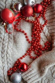 Świąteczna, przytulna, świąteczna atmosfera. świąteczne ozdobne bombki i czerwony sznureczek na dzianinowym swetrze.