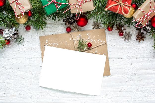 Świąteczna pusta kartka okolicznościowa z gałęziami jodły, dekoracjami, czerwonymi jagodami, pudełkami i szyszkami