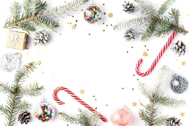 Świąteczna rama wykonana z gałęzi jodły śnieżnej, czerwonych cukierków, ozdób. boże narodzenie tło, tapeta. płaski układanie, widok z góry, kopia przestrzeń