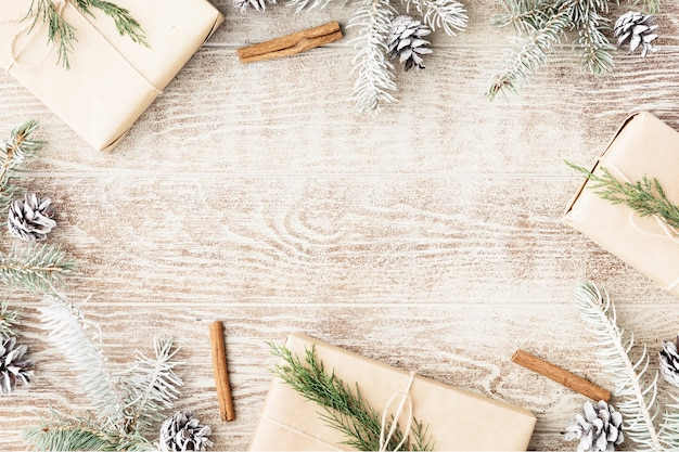 Świąteczna rama wykonana z gałęzi śnieżnej jodły, szyszek sosnowych, pudełka z brązowego papieru rzemieślniczego. świąteczna tapeta. płaski układanie, widok z góry, kopia przestrzeń