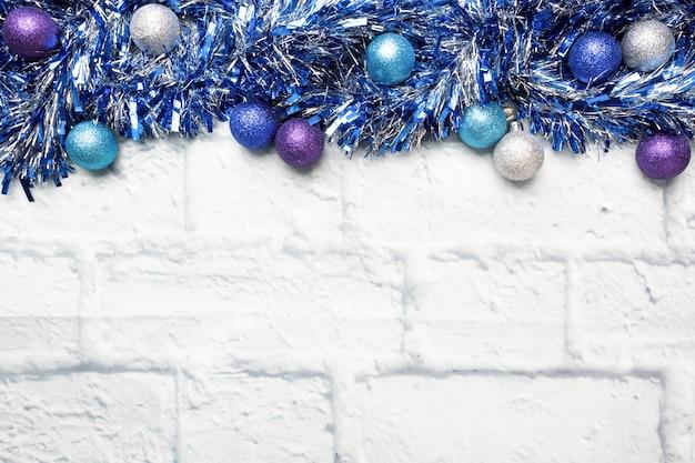 Świąteczna rama wykonana z ozdób choinkowych świecidełek w kolorze srebrnym i niebieskim na jasnym tle cegły. skopiuj miejsce leżał płasko.