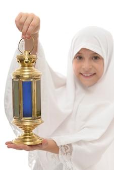 Świąteczna ramadan latarnia w rękach szczęśliwej muzułmańskiej dziewczyny