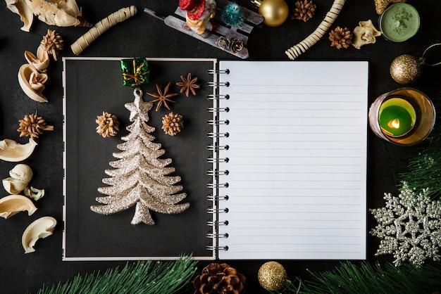 Świąteczna ramka świąteczna i vintage puste notatki otwartej książki na ciemnym stole