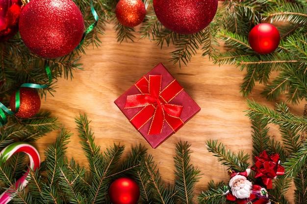 Świąteczna ramka wykonana z gałęzi jodłowych, pudełek na prezenty, czerwonych dekoracji świątecznych i cukierków