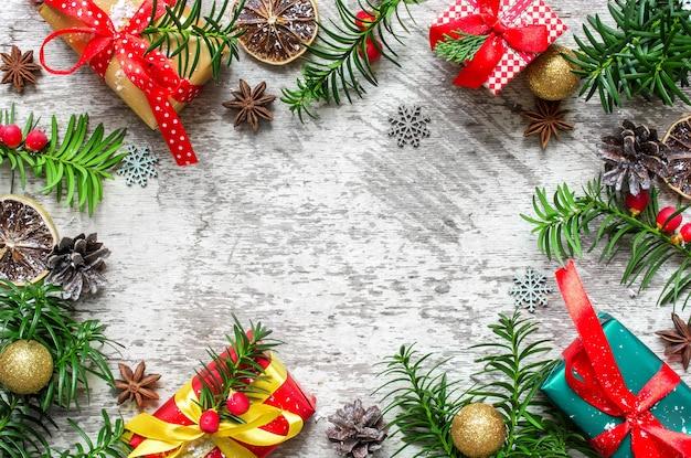 Świąteczna ramka wykonana z gałęzi jodłowych, pudełek na prezenty, czerwonych jagód