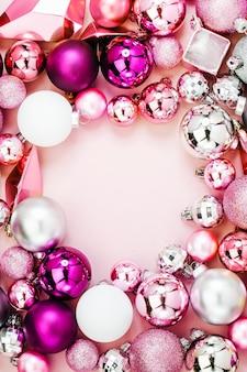 Świąteczna ramka wykonana ze stylowych świątecznych błyszczących bombek i złotych kryształków na pastelowym różowym tle. płaski układanie, widok z góry