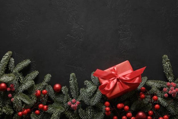 Świąteczna ramka z czerwonym prezentem i dekoracjami na czarnej świątecznej kartce z życzeniami