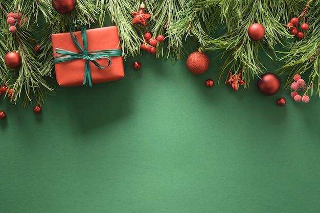 Świąteczna ramka z czerwonymi gałązkami sosnowymi i czerwonymi kulkami świąteczną kartkę z życzeniami
