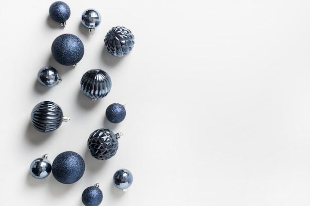 Świąteczna ramka z klasycznymi niebieskimi kulkami w neutralnej pastelowej szarości. widok z góry. świąteczna granica życzeń. karta z pozdrowieniami świątecznymi.