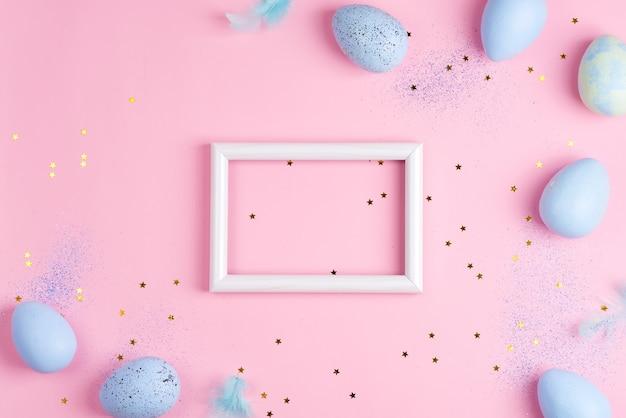 Świąteczna ramka z malowanymi jajkami w pastelowych kolorach niebieskim i dekoracją konfetti na jasnoróżowym tle.