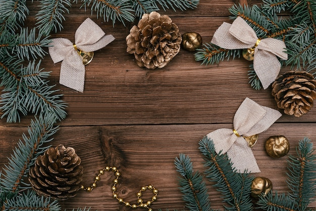 Świąteczna ramka z niebieskich gałęzi jodłowych, złotych szyszek i świątecznych dekoracji.