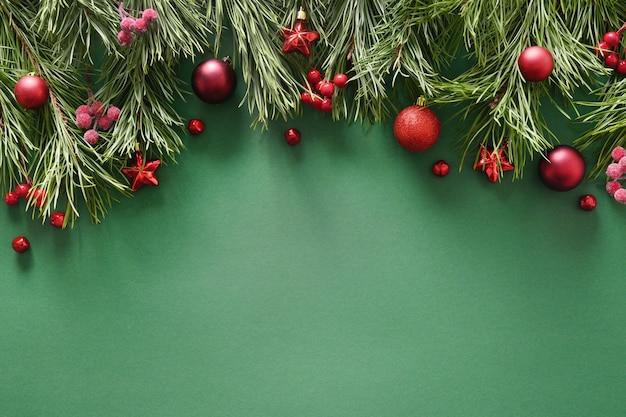 Świąteczna ramka z sosnowymi gałęziami czerwone kulki kartkę z życzeniami bożego narodzenia szczęśliwego nowego roku widok z góry mieszkania