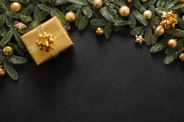 Świąteczna ramka ze złotym prezentem i dekoracjami na czarnej świątecznej kartce z życzeniami