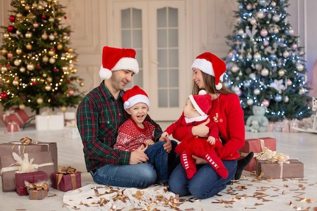 Świąteczna rodzina! szczęśliwa mama, tata i córeczka i syn w czapce świętego mikołaja. cieszący się miłością przytulania