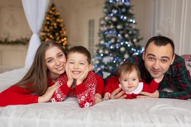 Świąteczna rodzina! szczęśliwa mama, tata oraz córeczka i syn, leżą. cieszące się uściskami miłości