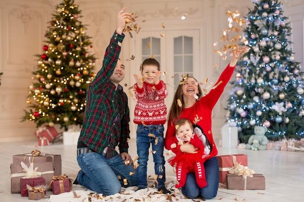 Świąteczna rodzina! szczęśliwa mama, tata oraz mała córka i syn. uściski miłosne, święta ludzie