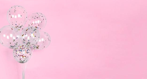 Świąteczna różowa ściana z balonami z błyszczącymi kolorowymi konfetti