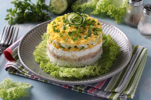 Świąteczna sałatka francuska z wątróbką dorsza, ryżem, jajkami, kukurydzą i ogórkiem na talerzu na jasnoniebieskim tle.