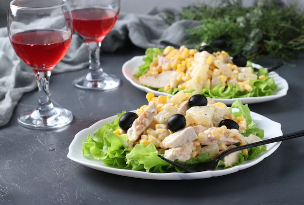 Świąteczna sałatka z ananasem, pieczonym kurczakiem, kukurydzą i czarnymi oliwkami na białych talerzach oraz dwa kieliszki czerwonego wina na szarym stole. format poziomy