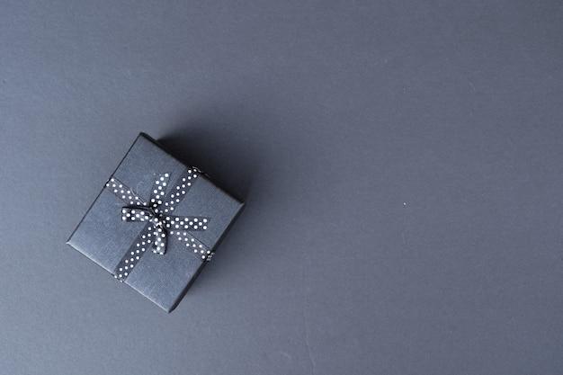 Świąteczna scena płaskiego świecenia z pudełkiem prezentowym w minimalistycznym czarnym kolorze
