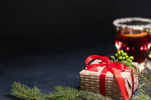 Świąteczna ściana bożego narodzenia. prezent zawinięty w papier rzemieślniczy przewiązany czerwoną wstążką na ciemnej ścianie. grzane wino, ozdoby z gałęzi jodły.