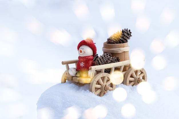 Świąteczna ściana bożego narodzenia z bałwanem na drewnianym wózku. szczęśliwy bałwan w zimowy boże narodzenie krajobraz. wesołych świąt i wesołych świąt