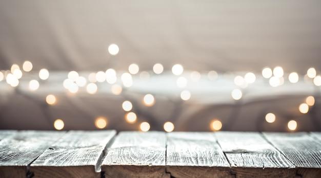Świąteczna ściana świąteczna z pustym drewnianym blatem nad świątecznym światłem bokeh.