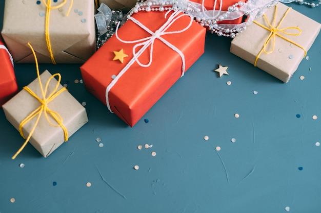 Świąteczna ściana uroczystości świątecznych. asortyment prezentów zawiniętych w czerwony i rzemieślniczy papier. pudełka prezentowe łączą się ze srebrnymi sznurkami z koralików i dekorem konfetti. wolna przestrzeń