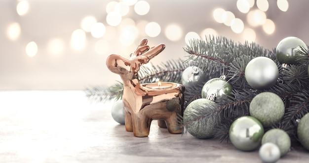 Świąteczna ściana ze świecznikiem, choinką i zabawkami choinkowymi.