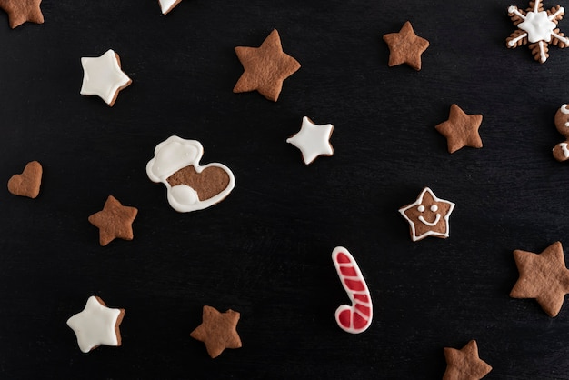 Świąteczna skarpeta i gwiazdy z piernika na czarnym tle. tradycyjne wypieki.