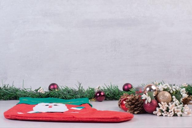 Świąteczna skarpeta pełna świątecznych kulek na białej powierzchni