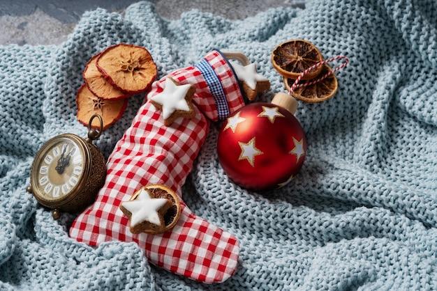 Świąteczna skarpeta wypełniona gwiazdkowymi ciasteczkami i ozdobiona suchymi pomarańczami, zegarem i świąteczną zabawką na niebieskiej kratę. przytulna koncepcja bożego narodzenia