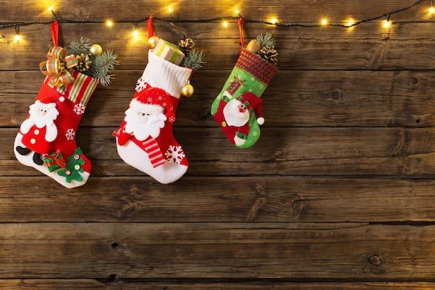 Świąteczna skarpeta z prezentami wiszącymi na ciemnym starym drewnianym backgro