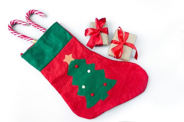 Świąteczna skarpeta z pudełkami prezentowymi i sztabami karmelu na białym tle.