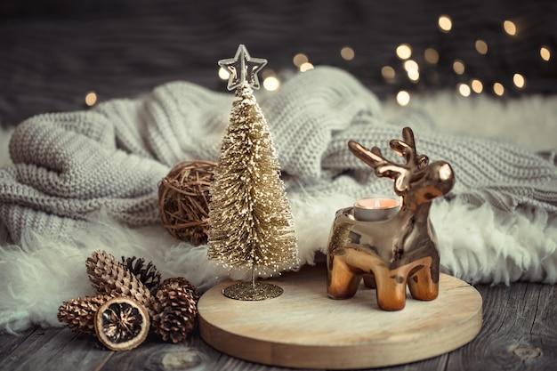 Świąteczna świąteczna ściana z zabawkowym jeleniem z pudełkiem i choinką, rozmyta ściana ze złotymi światłami na drewnianym stole pokładowym