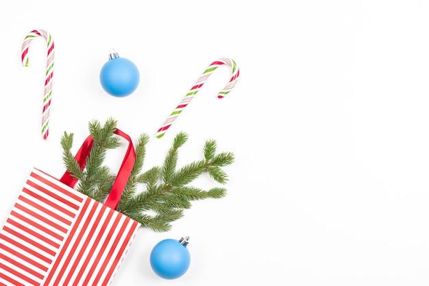 Świąteczna torba prezentowa z gałązką jodły, cukierkami i niebieskimi bombkami dekoracyjnymi