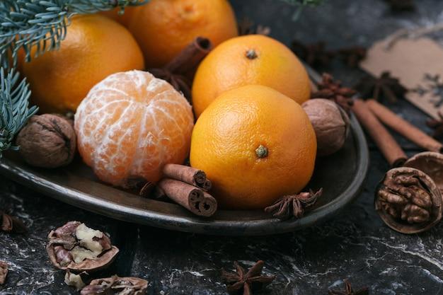 Świąteczna treść, mandarynki, orzech, cynamon, kardamon, metalowe naczynie, świerkowa gałązka, ciemnobrązowe tło, poziome