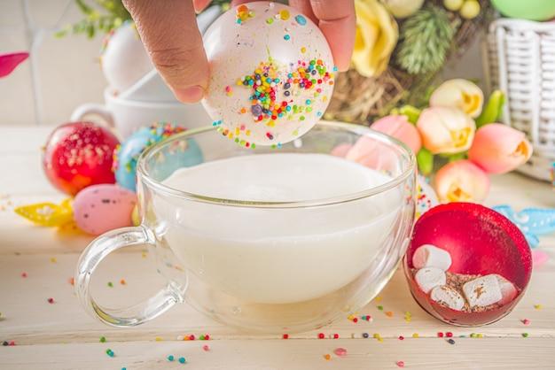 Świąteczna wielkanocna bomba z gorącej czekolady. bomba z białej czekolady do gorącego napoju kakaowego, z pianką i posypką cukrową