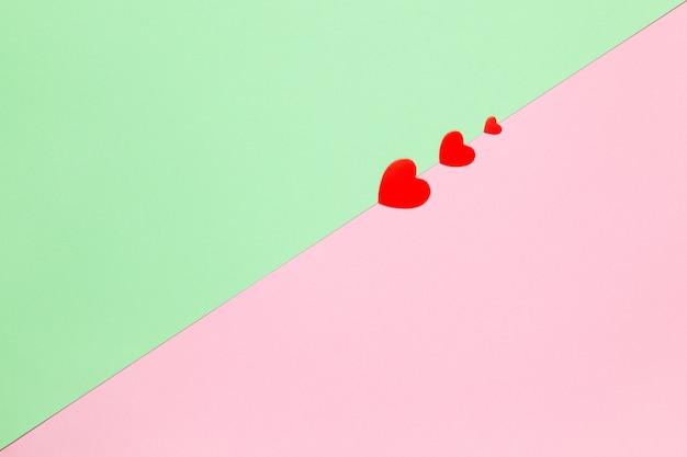 Świąteczna wiosna leżała płasko. trzy czerwone serca na pastelowym dwukolorowym tle różowy i zielony, miejsce.