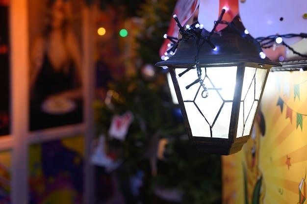 Świąteczna wisząca latarnia w stylu vintage ze świecącymi światłami girland świeci na ulicy w nowy rok w noc