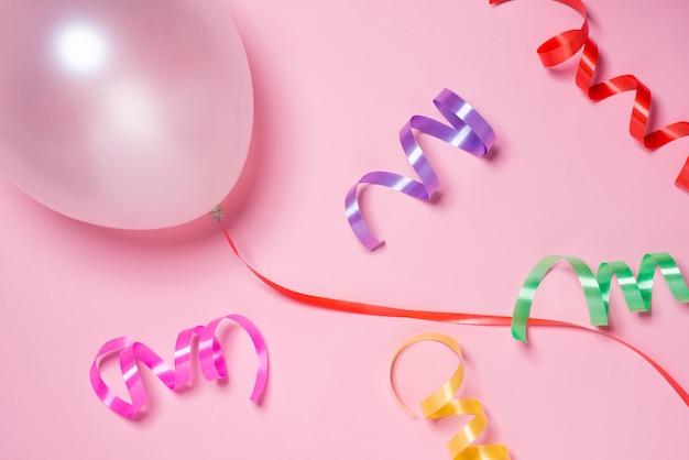 Świąteczna wstążka i biały balon na różowym tle