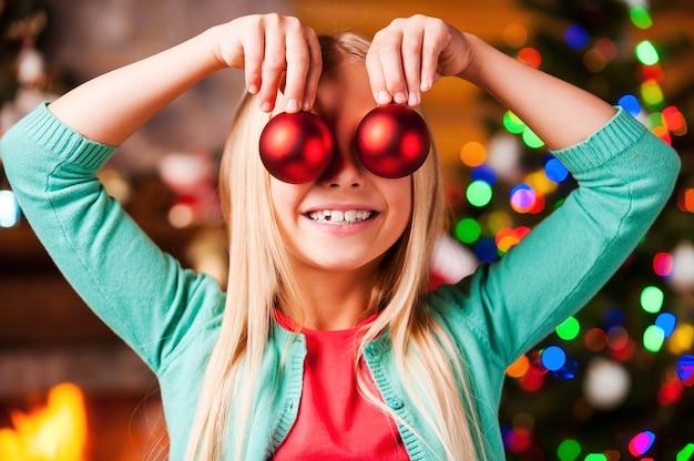 Świąteczna zabawa. śliczna mała dziewczynka trzymająca bombki przed oczami i uśmiechająca się z choinką i kominkiem w tle